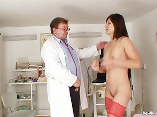 She dressed in stockings to tempt her doctor and he has fun looking inside her pussy.