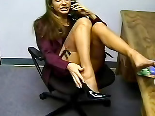 The secretary takes a call and rubs her sexy feet in soft nylons to make it an arousing tease video.