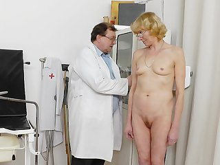 Mature blonde Anna is lying on the medical chair and masturbating with some tools