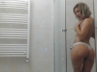 Blonde busty chick teasing and fingering her wet cunt in the shower.