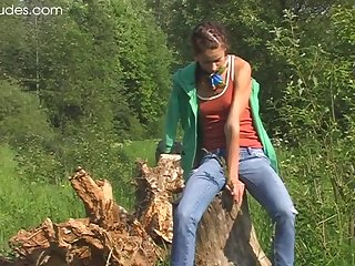 Compelling girl plays with her shaved beaver in the wilderness