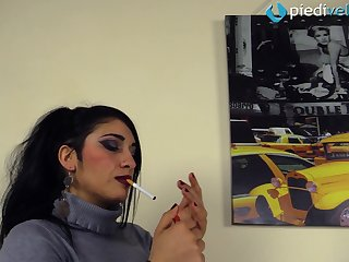 She shows her feet in nylons while having a cigarette