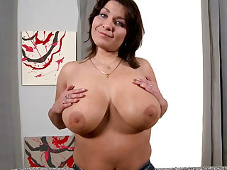 Mature babe with giant boobs Sophia Moroe is taking off her bra and tight panties on the camera