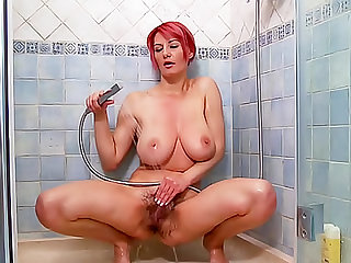 The big breasted chick with pretty pink hair and a hairy vagina takes a shower and masturbates.