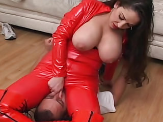 Her bright red leather catsuit is skintight and sexy as she dominates and sits on his face.