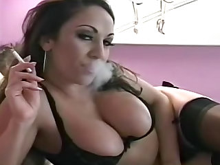 Take a look at this brunette MILF with big tits wearing nylon stockings and smoking a cigarette on the bed in this fetish video.