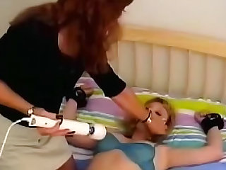Watch this femdom using handcuffs on her submissive who's also wearing a gag. This MILF lesbian slave is getting a vibrator rubbed in her crotch.