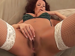 Carol Sunshine is wearing a bra and stockings in this video. Watch this brunette with big tits masturbating her love tunnel again and again.