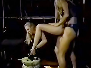 Blonde lesbians with big tits wearing a latex outfit are fucking each other with a strapon in the dungeon.