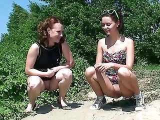Dasha and her Russian brunette companion are showing an upskirt of their shaved pussies in this video with a close up in which they are pissing outdoors.