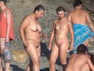 Stunning mature nudists are getting naked outdoors and playing with shaved pussies