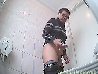 Mom with short hairs is taking off her pants and pissing in close-up scene on the voyeur cam