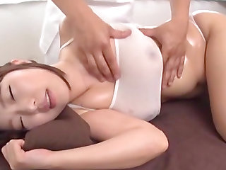 Oiled up Japanese woman lets a horny masseur play with her body