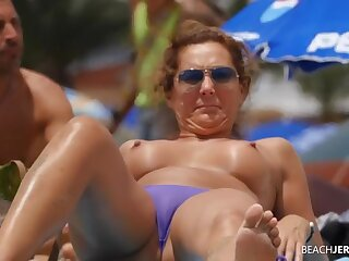 Topless milf gets some sun in the sand