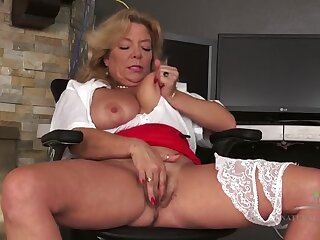 Secretary sits at her desk and rubs mature pussy