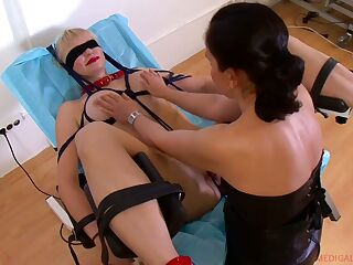 Lesbian gynecologist examines pussy of tied up busty blond milf