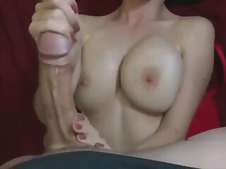 A girl jerks off a dick with both hands and gets cum on her chest
